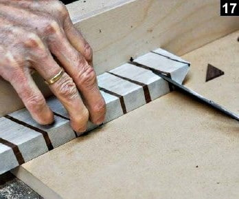 Un paquet de lames de bois foncé est coupé pour réaliser plusieurs onglets