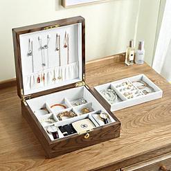 Vue de 3/4 de la boîte à bijoux en bois carrée (ouverte , avec bijoux et posée sur tables)