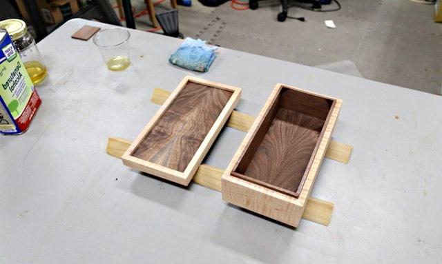 La boîte à bijoux en bois simple et son couvercle sont en cours de vernissage