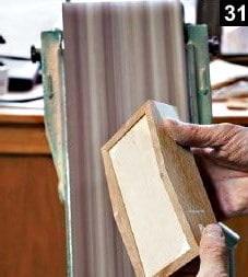 Les côtés de la boîte à bijoux en bois rectangulaire sont poncés avec une ponceuse à bande