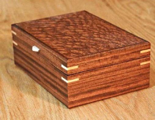 Vue de 3/4 de la boîte en bois plaqué, fermée et posée sur une table