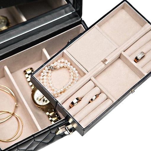 Boîte remplie de bijoux vue de dessus avec son plateau amovible soulevé