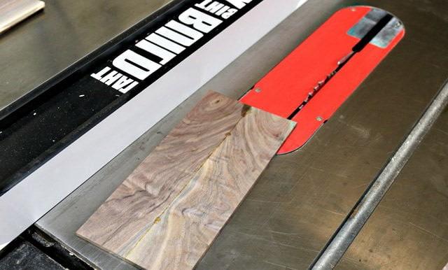 Une planche de bois de noyer brut est coupée dans sa longueur
