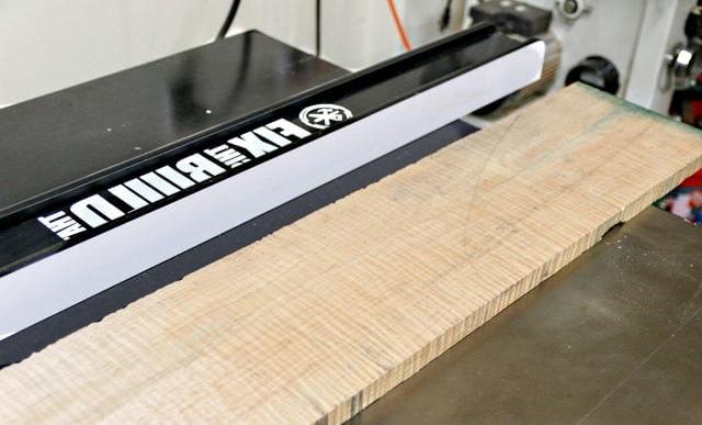 Une grande planche d'érable est posée sur une table de ponçage