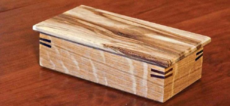 Boîte à bijoux en bois rectangulaire finie, refermée et posée sur une table