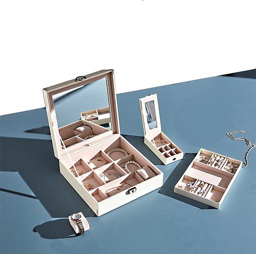 Vue de l'ensemble des compartiments de la boîte à bijoux simili cuir blanc, posés sur une table