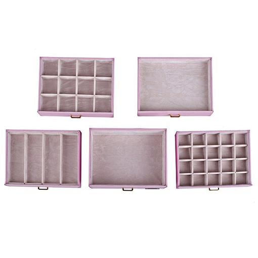 Vue aérienne présentant les tiroirs (vides et posés sur une table) de la grande boîte à bijoux en cuir rose à portes