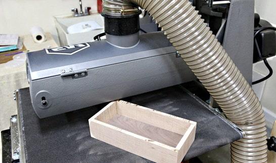 La boîte est introduite de biais sous la ponçeuse pour une reprise de la partie supérieure