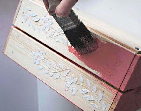 Un coup de pinceau est appliqué sur le bois brut d'une boîte
