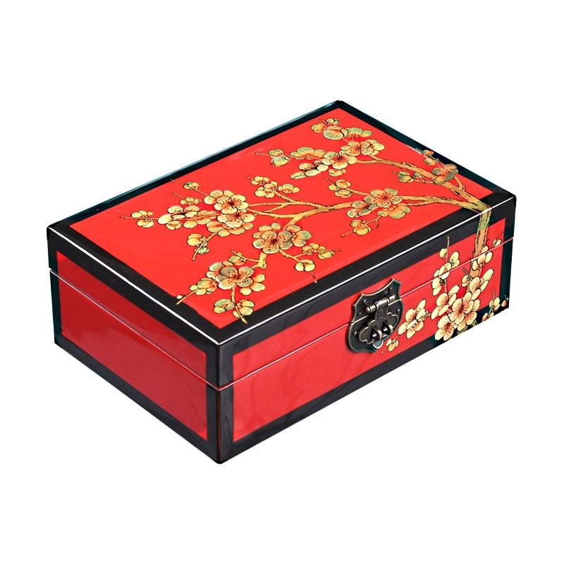Vue de 3/4 du dessus de la boîte représentant les fleurs d'un cerisier sur fond rouge et arêtes noires